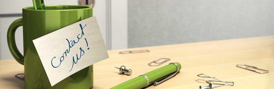 Green coffee mug and pen on light wood desk